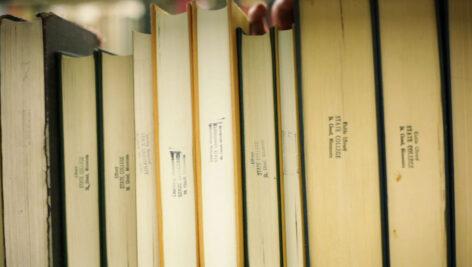 فوتیج ویدیویی حرکت پن روی ردیف کتابها در کتابخانه